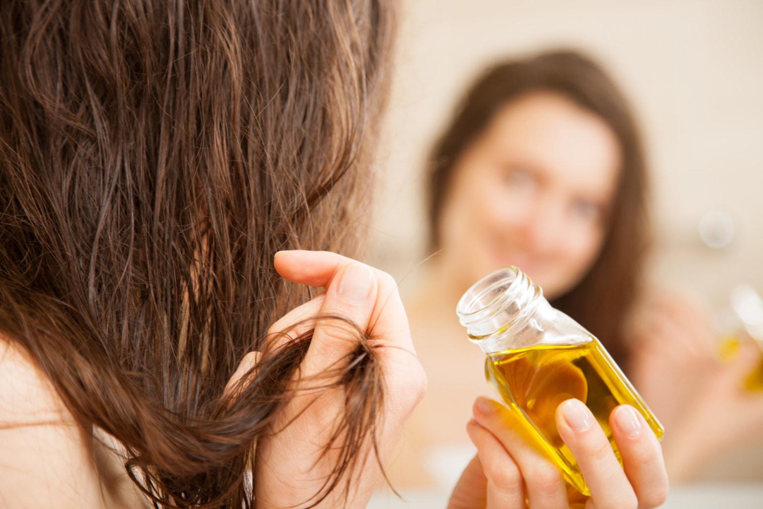 portrait d'une femme en train de faire un bain d'huile pour ses cheveux