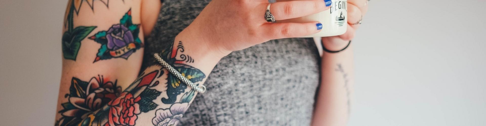portrait d'une femme qui boit un thé et qui a les bras tatoués
